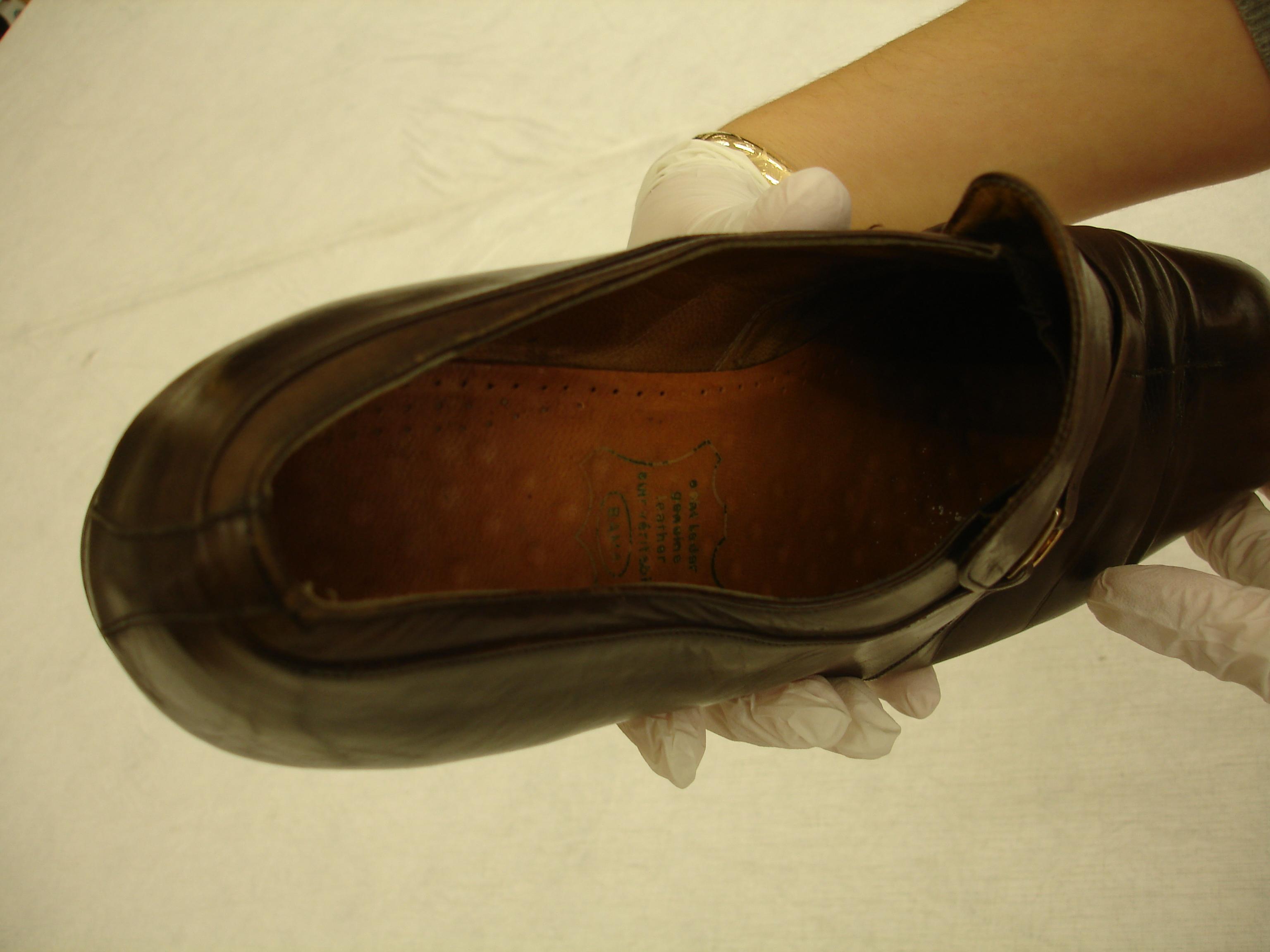 gloved hands handling old shoe