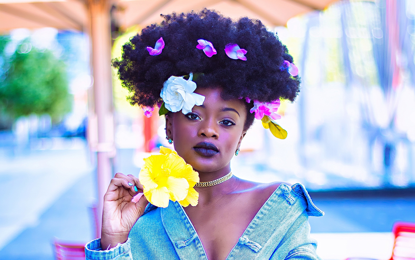 Female model posing with flowers in her hair and denim jacket