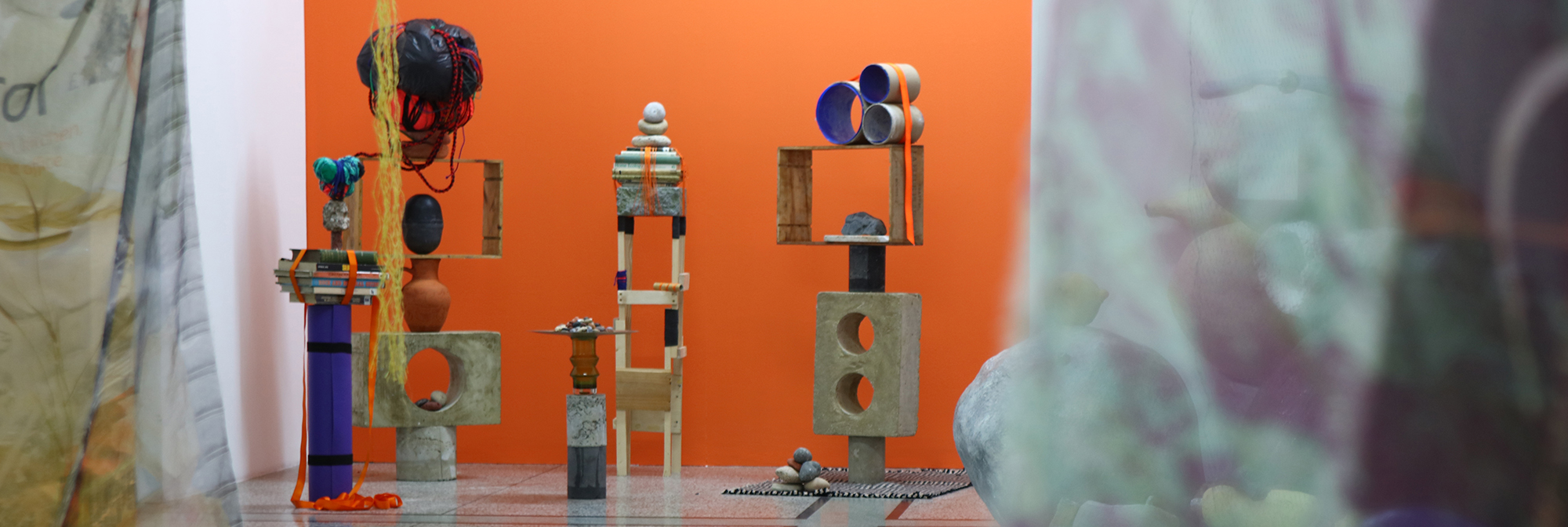 Exhibition installation shot featuring five assemblage sculptures against a bright orange wall, with draped printed fabrics in the foreground.