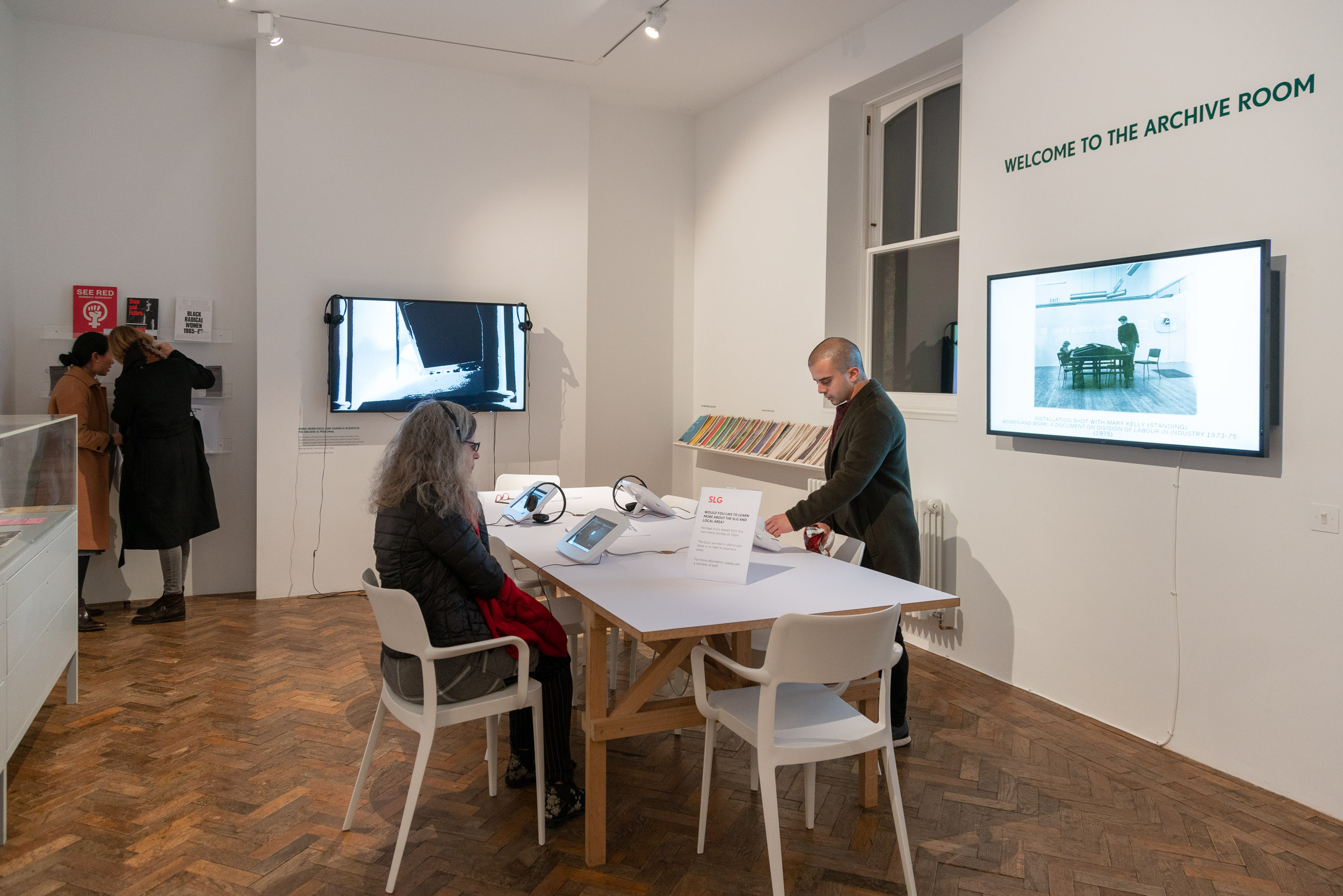 People looking at screens and works which are displayed on a white table