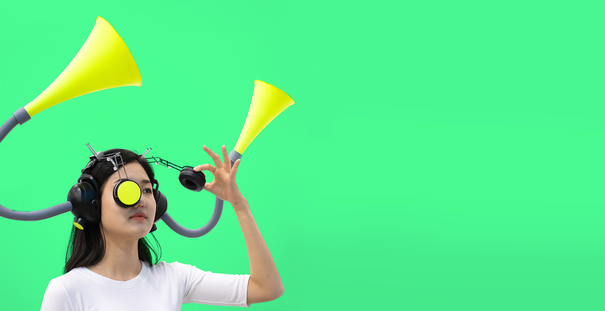 Figure wearing mask with yellow trumpets against bright green background
