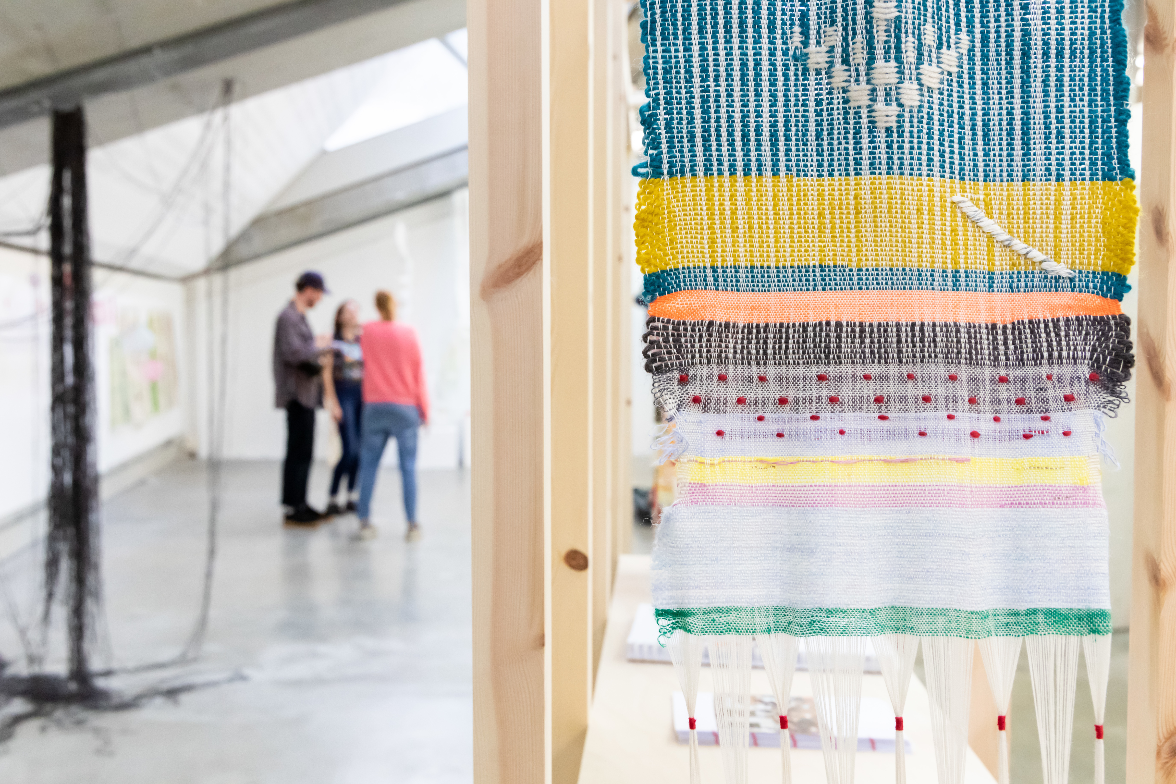 Colourful textiles work with people in background