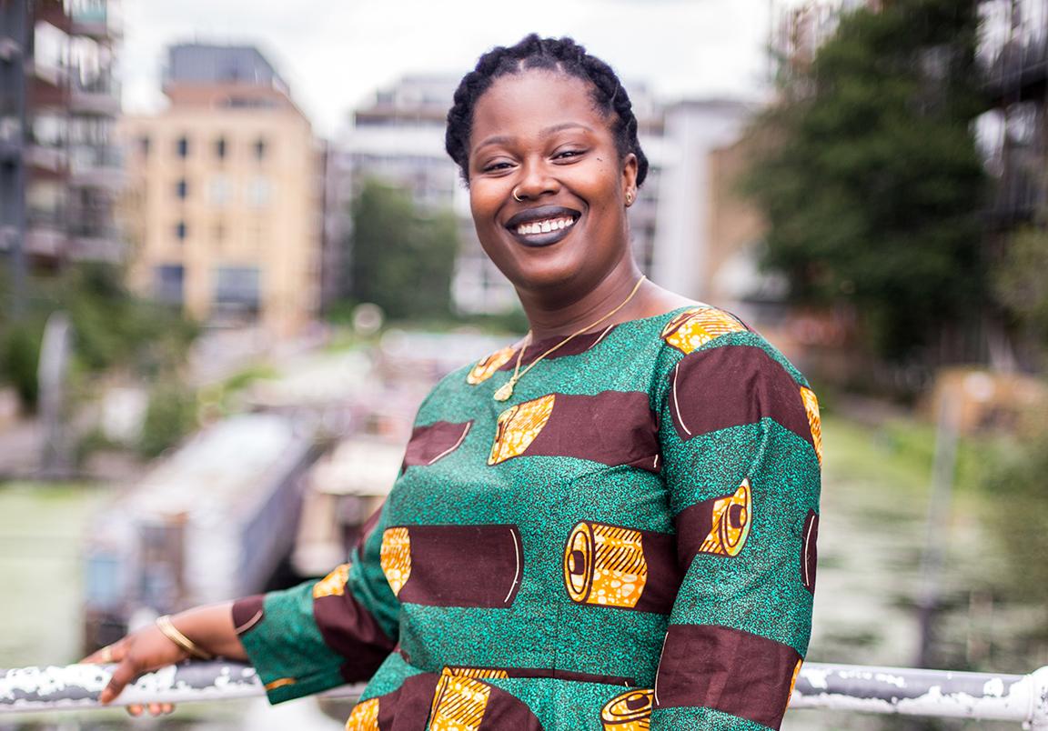 Founder of Black Women in PR Deborah Marie, standing outside near residential buildings.