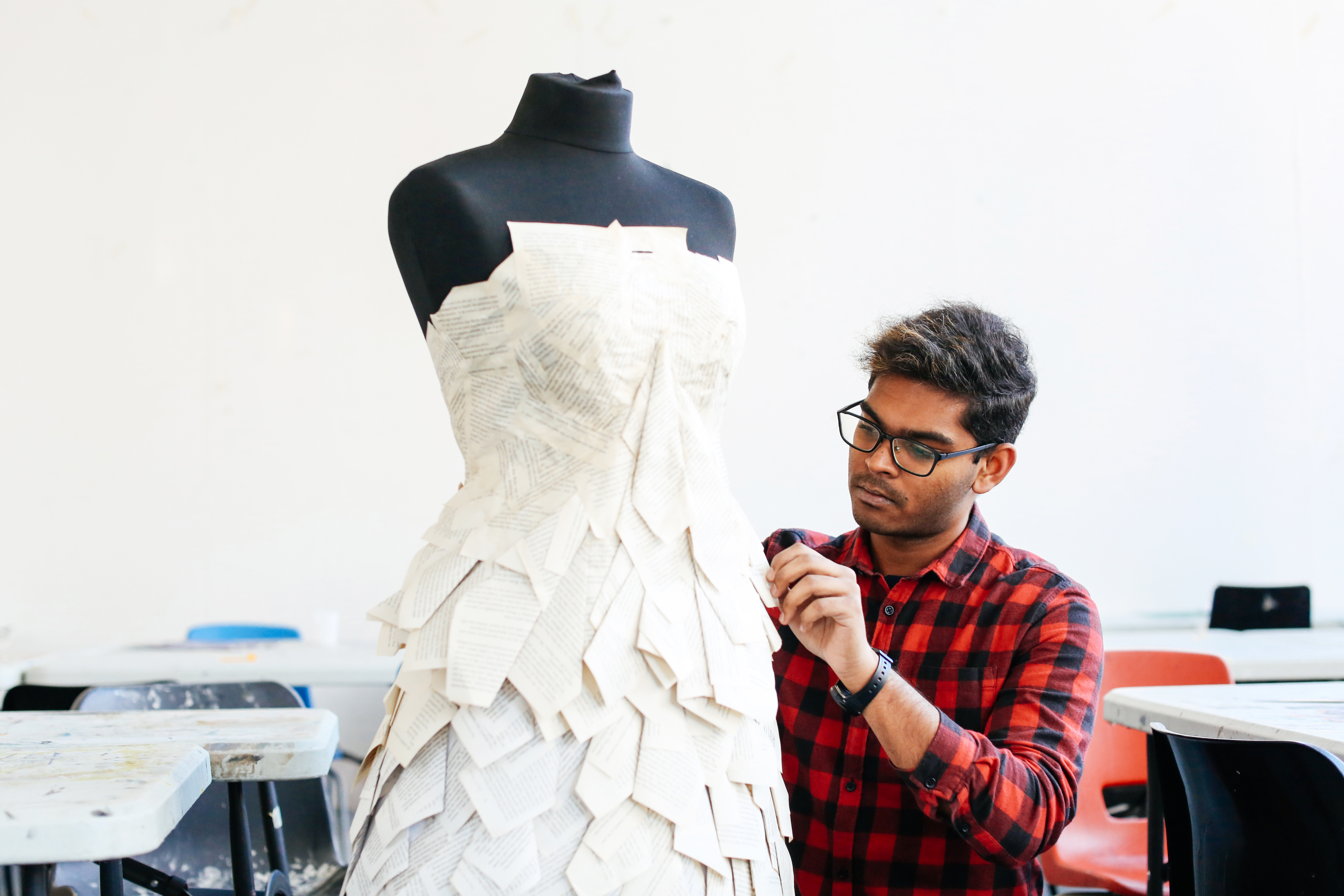 UAL student Pavithiran Charlas working on a dress displayed on a mannequin.
