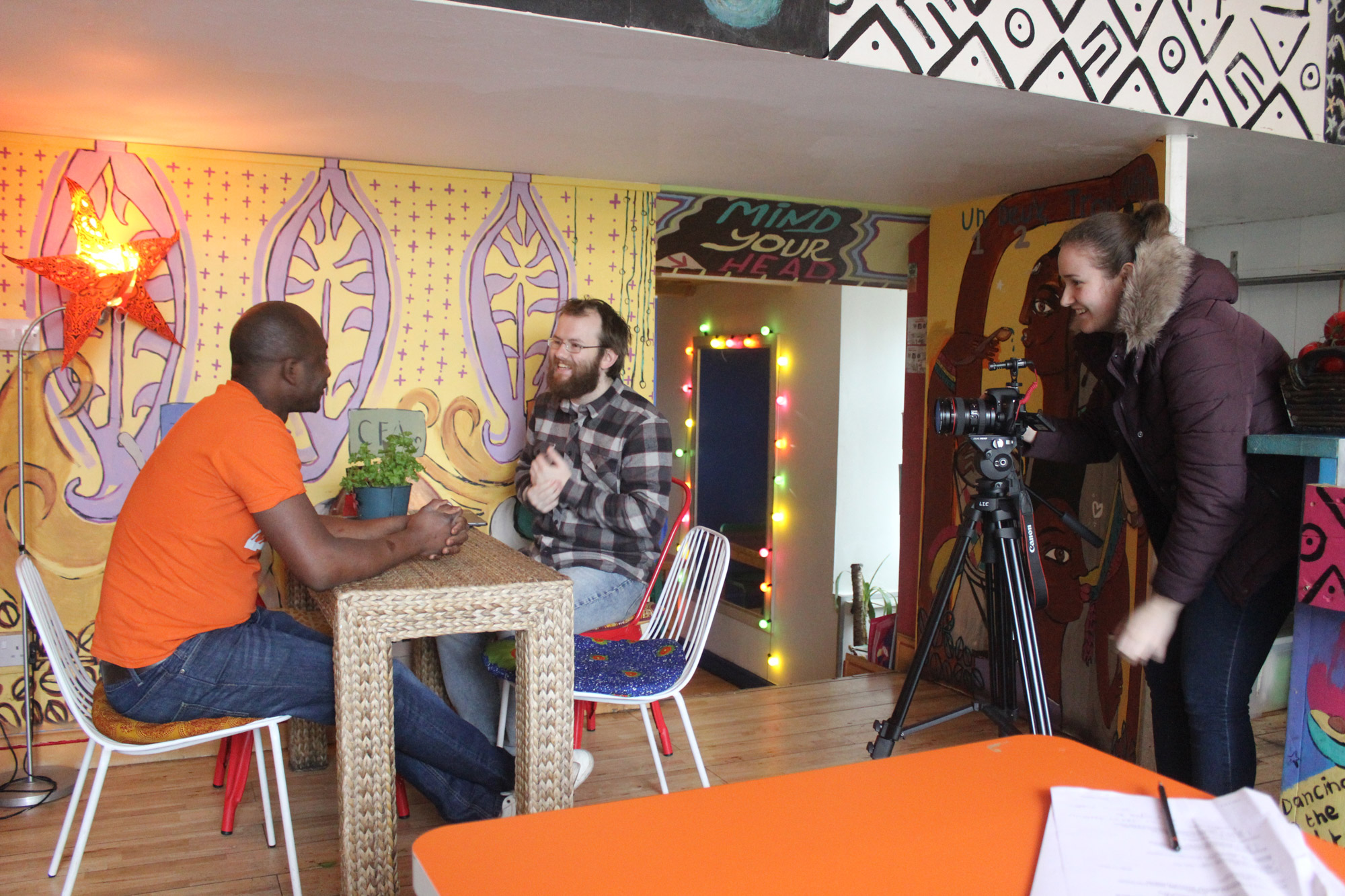 Two men, one client and one student, sit on a table in a cafe while a camera-woman films