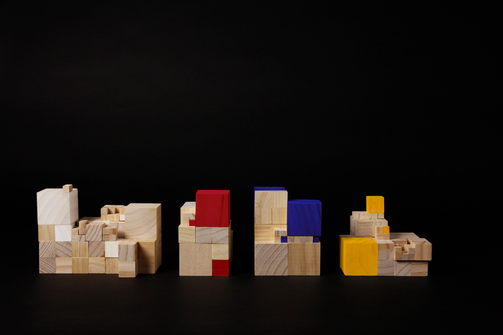 Wooden cube bricks, some coloured in red, yellow and blue, stacked into piles.