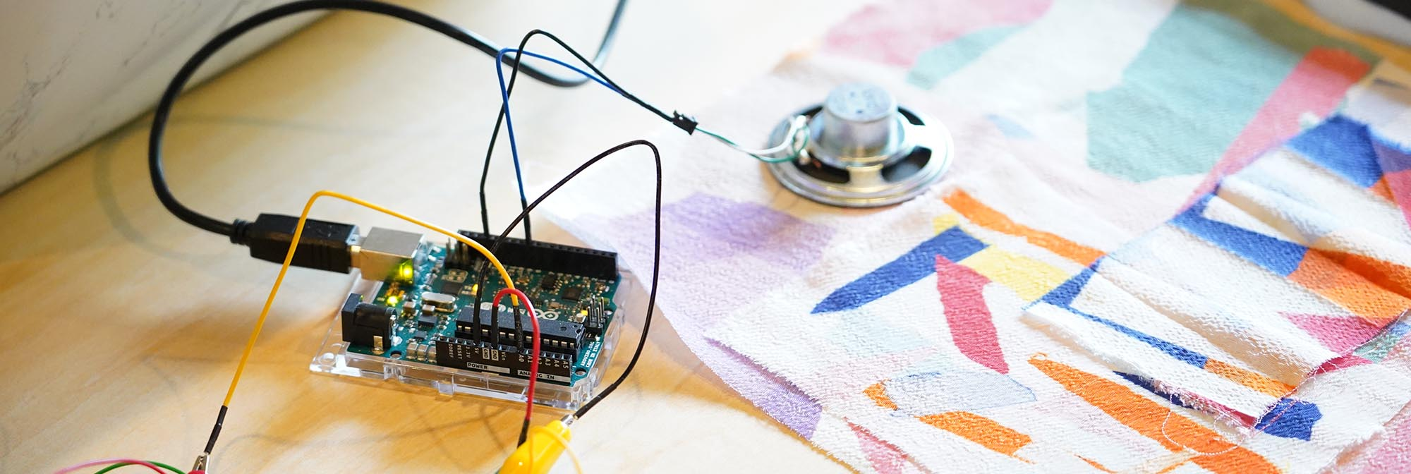 Close-up photograph of some wires and a mental sensor attached to a colourful patterned fabric sample.