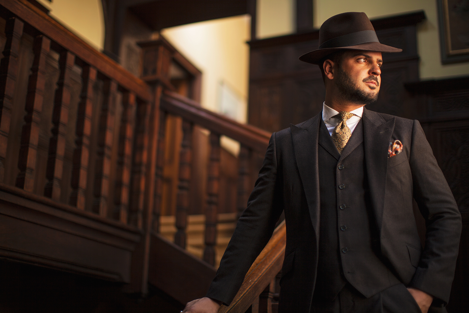 Man wearing tailored suit and hat posing in stairs