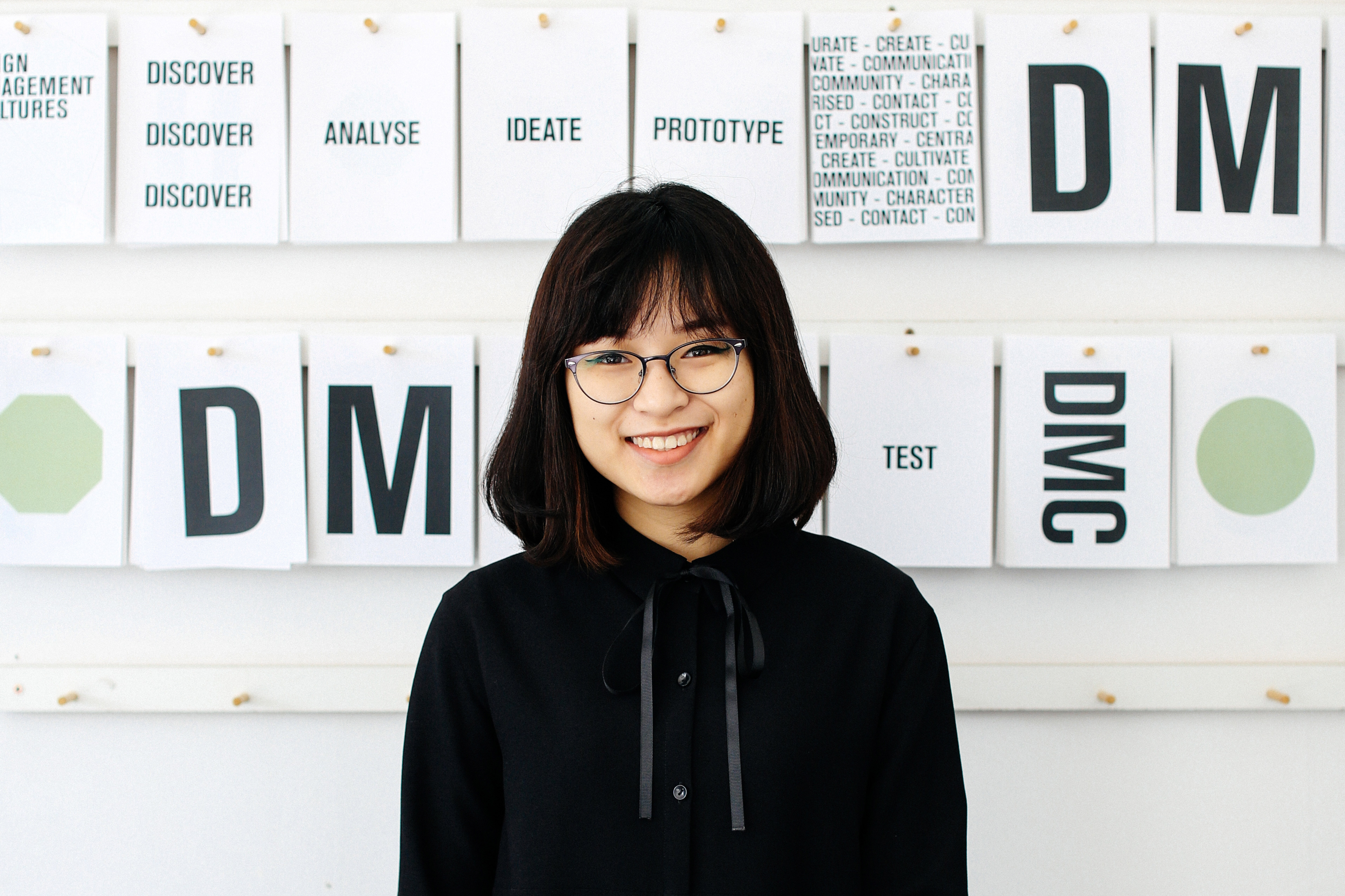 Student Ngoc (Sam) Trieu, BA (Hons) Design Management, in front of her graphic design installation at London College of Communication