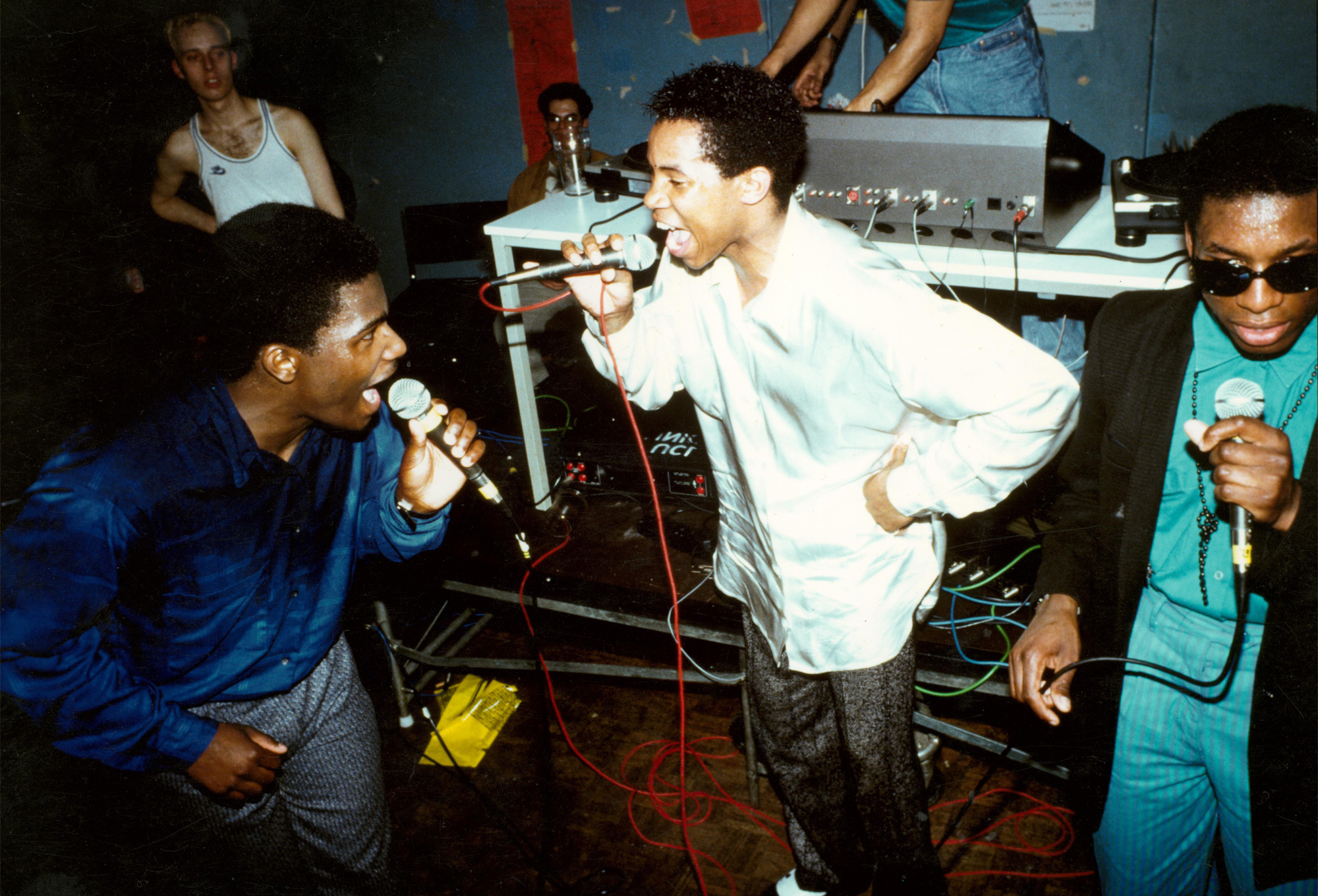 Three people standing together as a group singing into microphones in a club setting