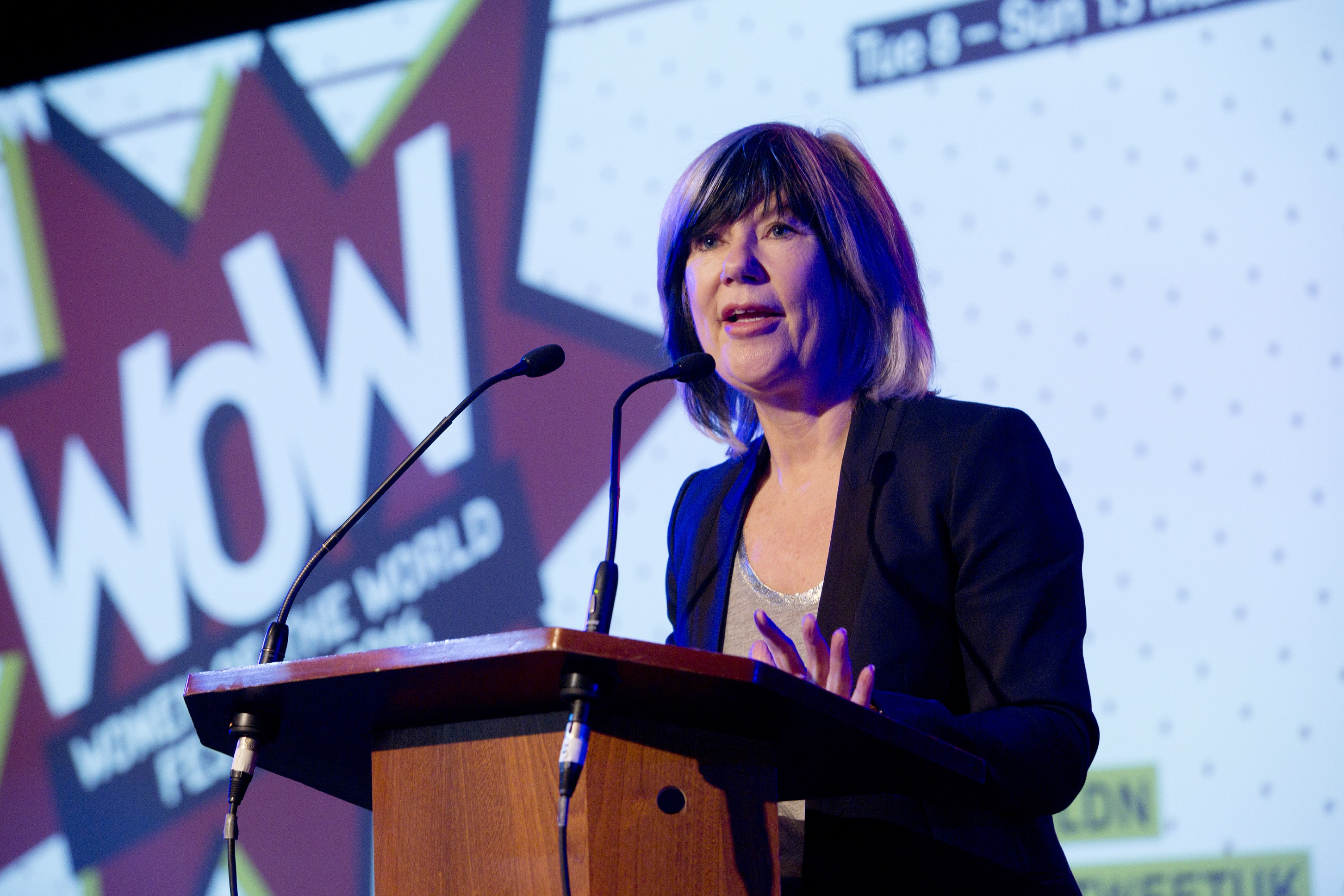 Woman at lectern with screen with WOW logo in background