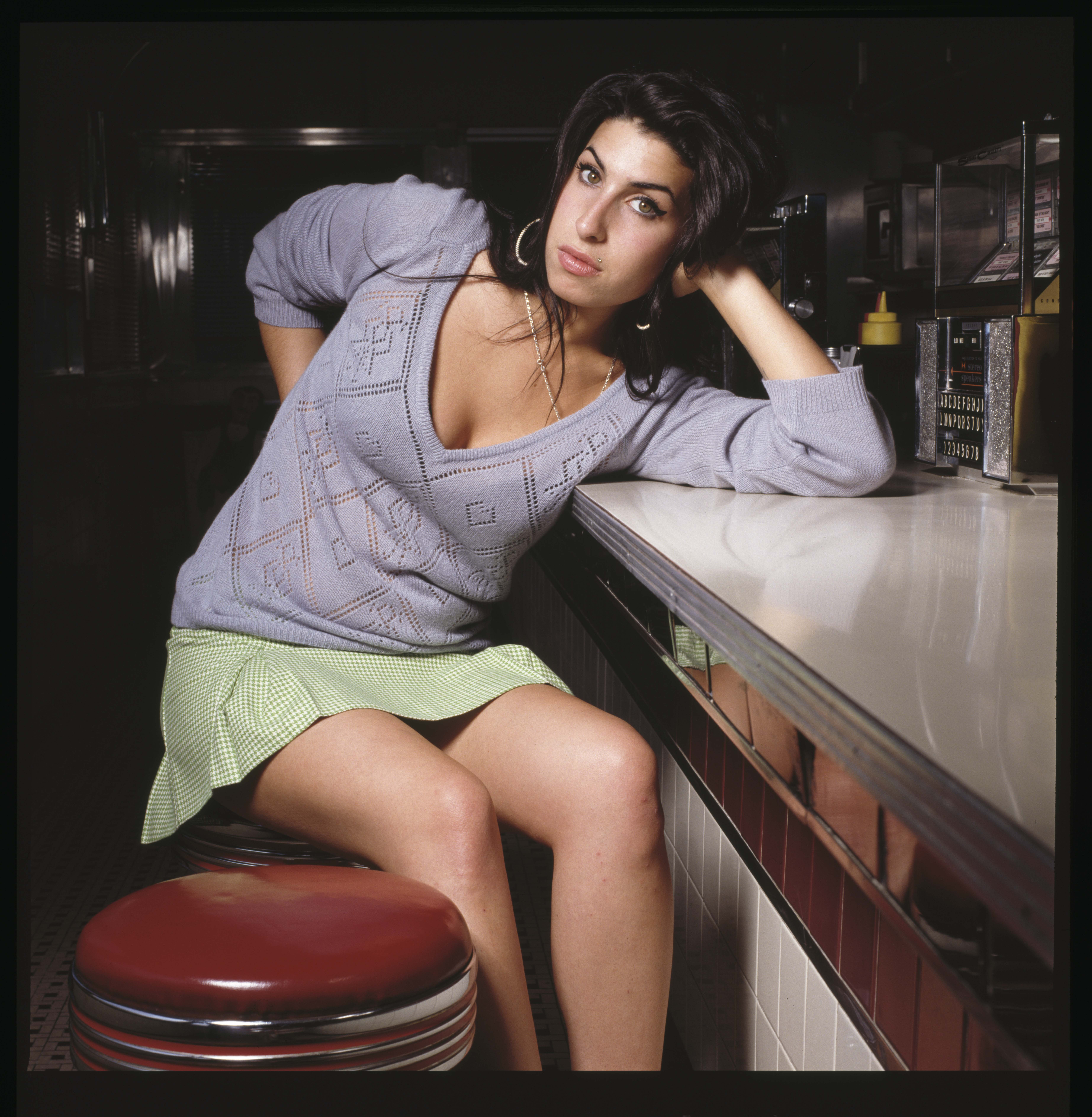 Amy Winehouse leaning against a bar