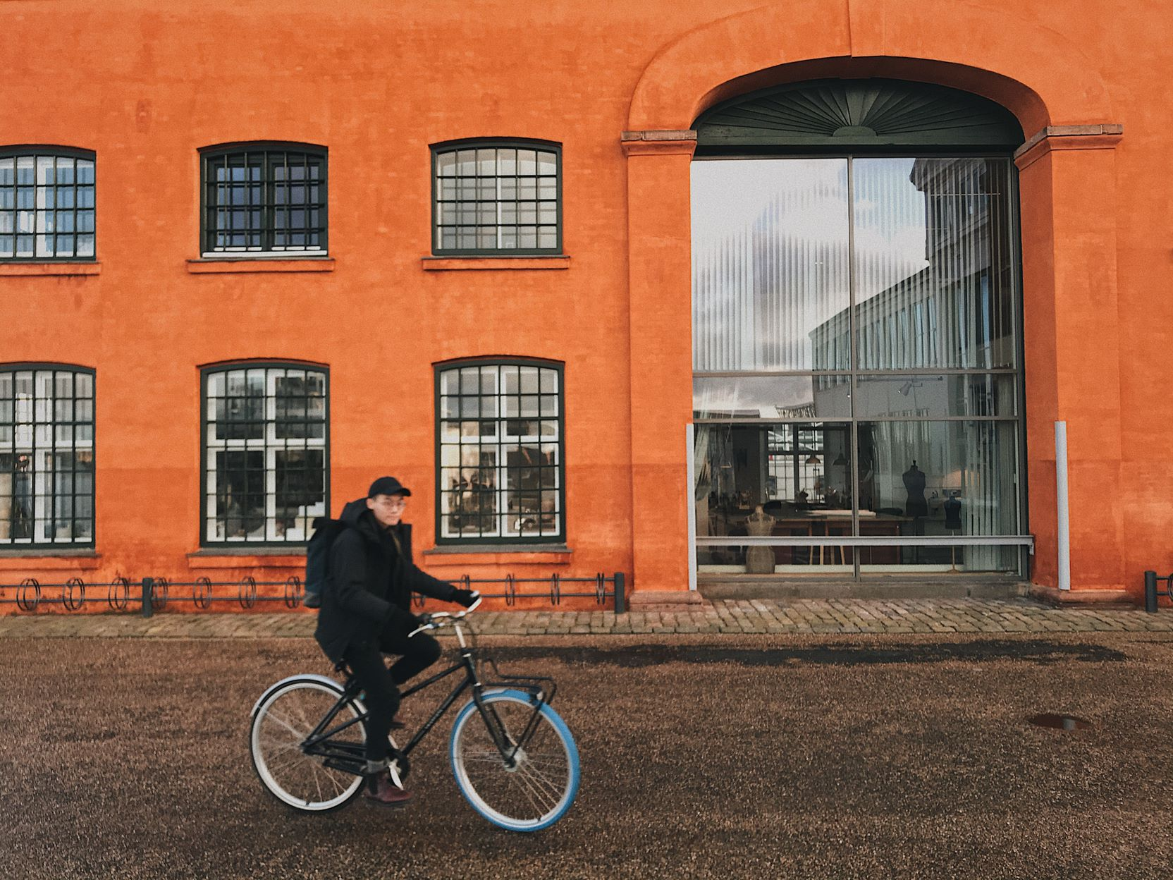 A bright orange building in the background with a young Asian man on a bike cycling past it