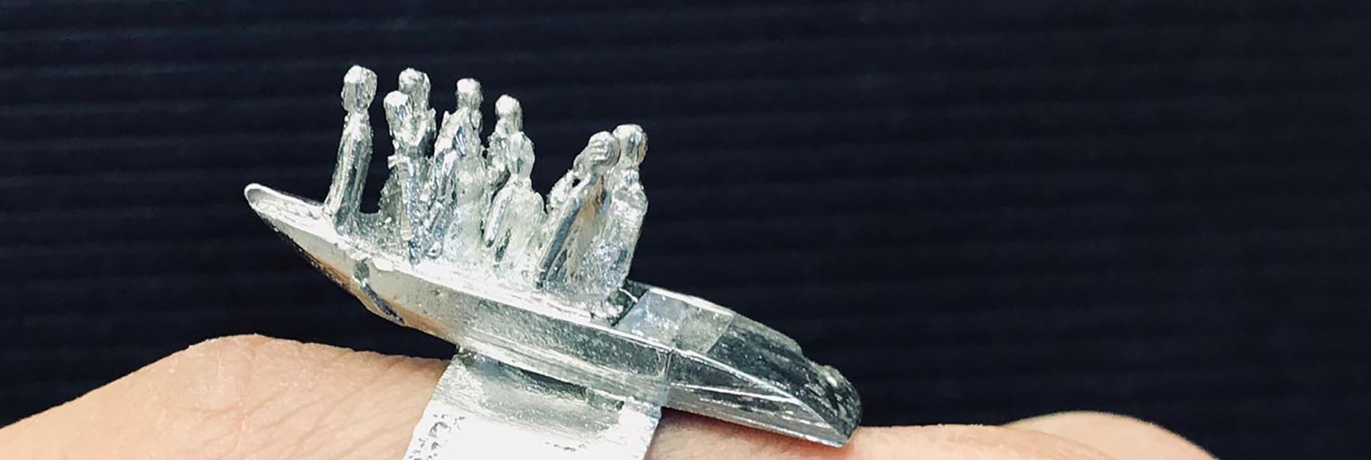 Close up of a pewter ring in the form of people standing in a boat.