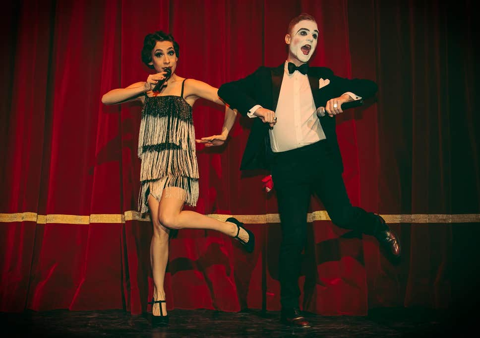a male and female on stage in front of red curtain dancing, one in 60s outfit, other with painted face