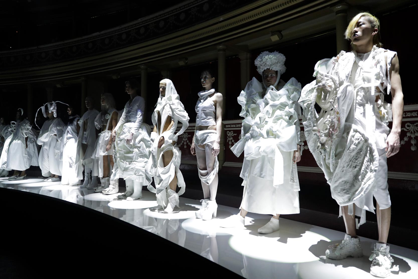 Models wearing white garments standing along catwalk
