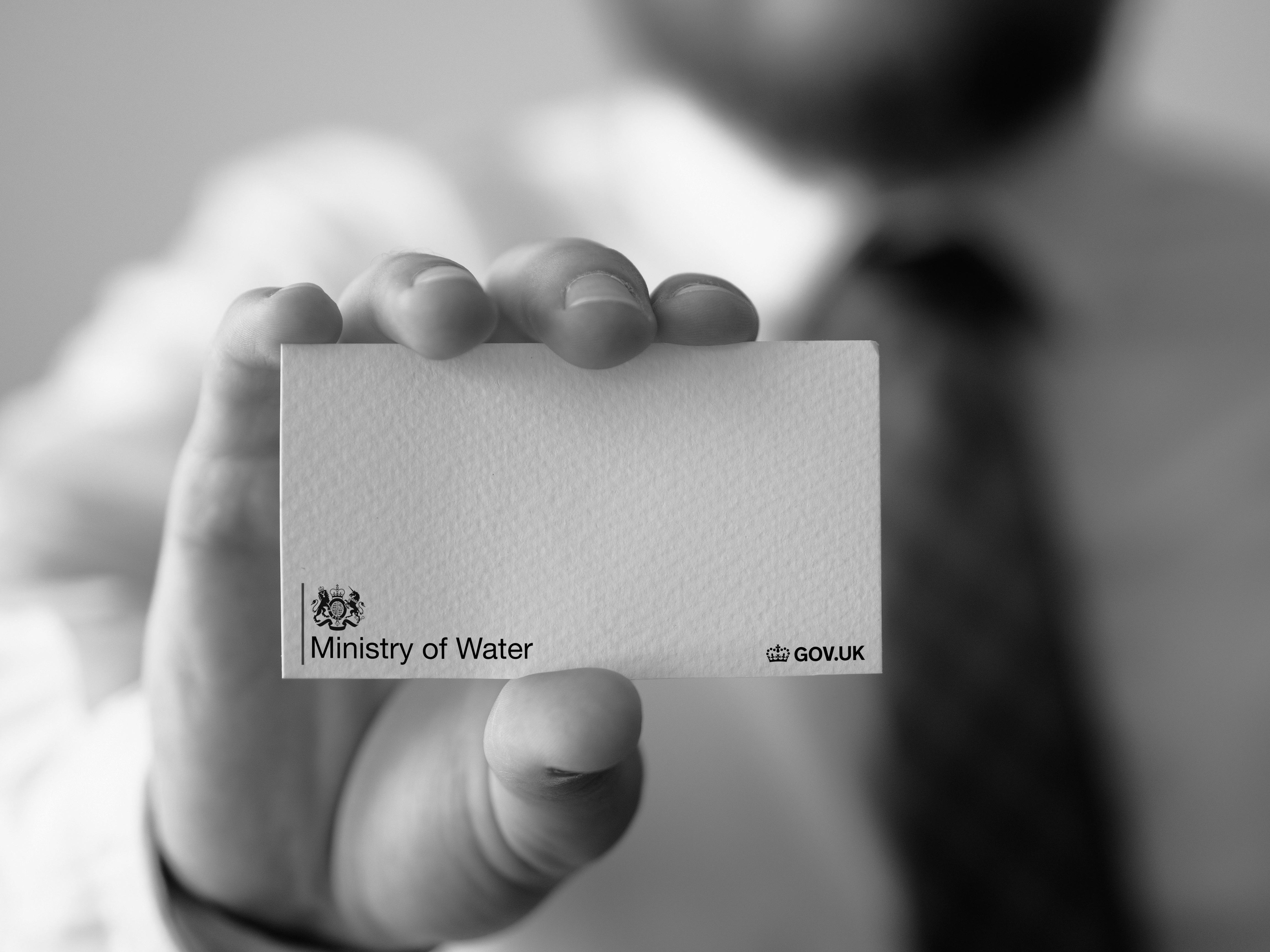Black and white image of hand holding business card from Ministry of Water