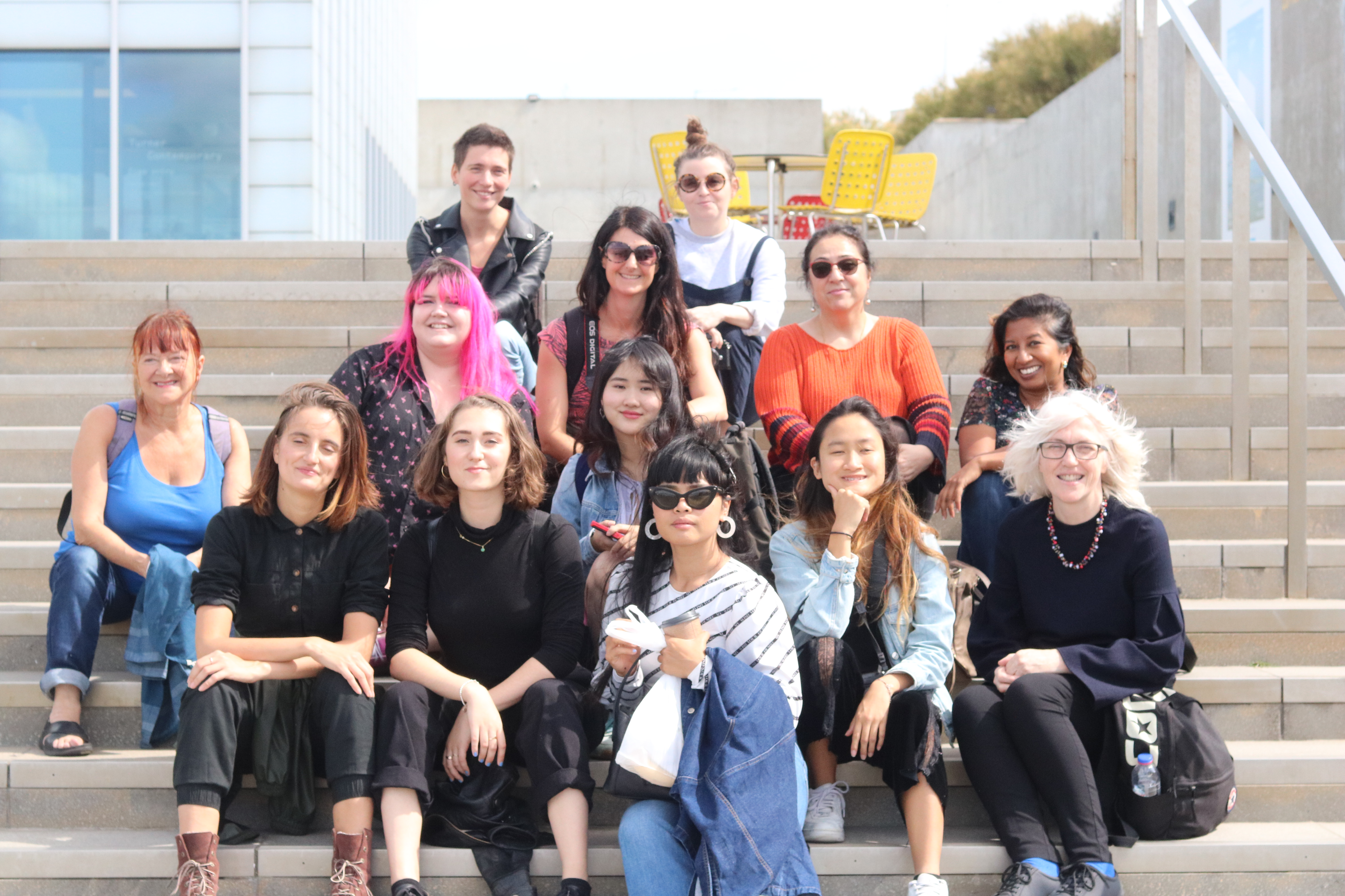 Group Photo of students who came on the annual Post-Grad Community Margate Trip sitting on steps of Turner Contemporary Gallery
