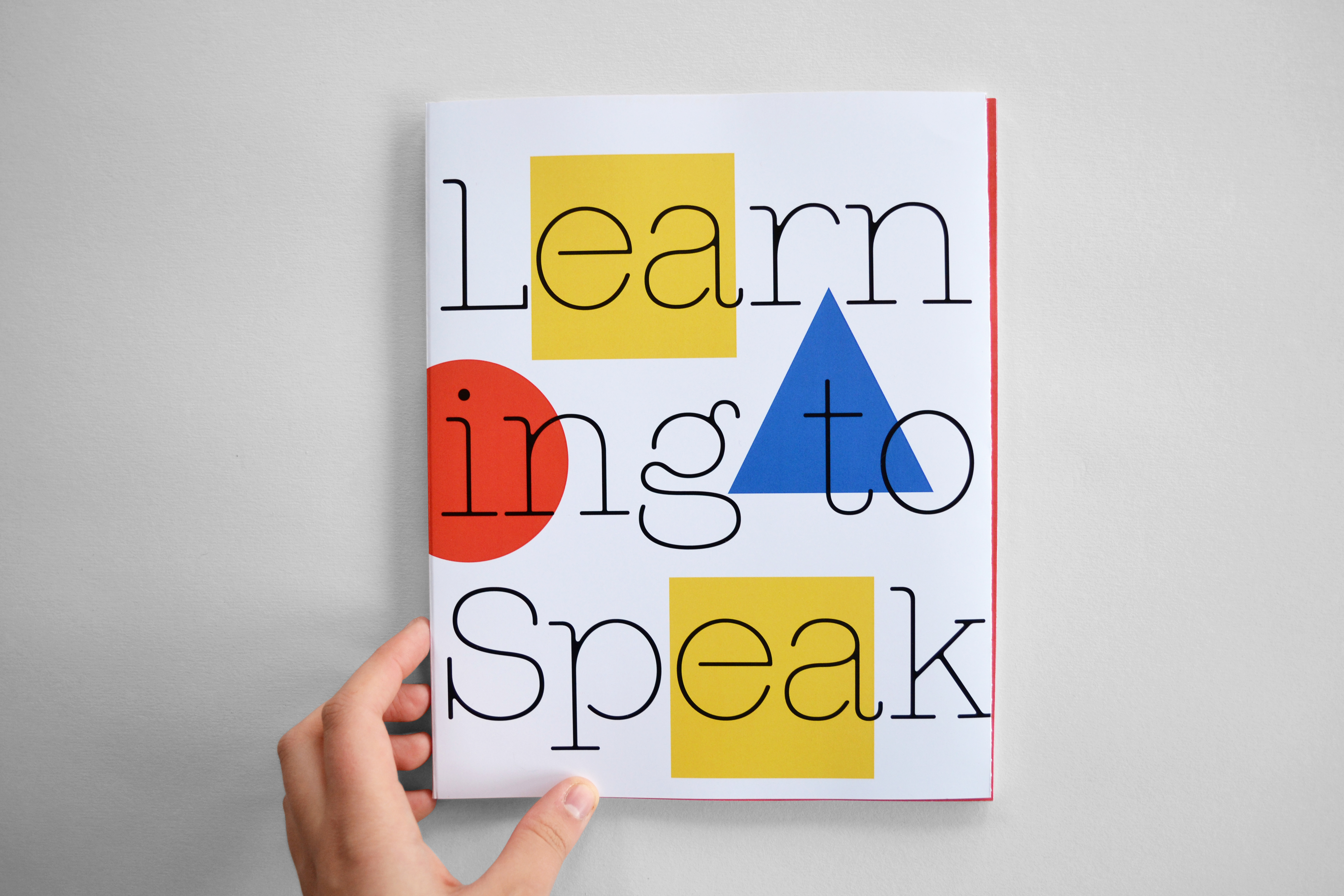 A hand holds small book with colourful shapes. Text reads 'learning to speak'