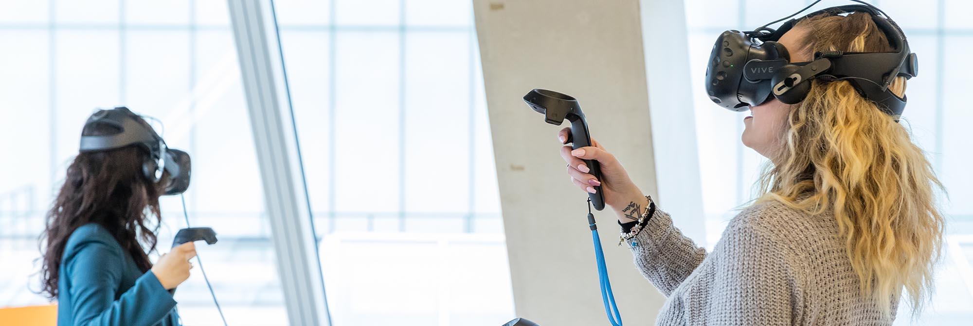 Two women wearing virtual reality headsets.