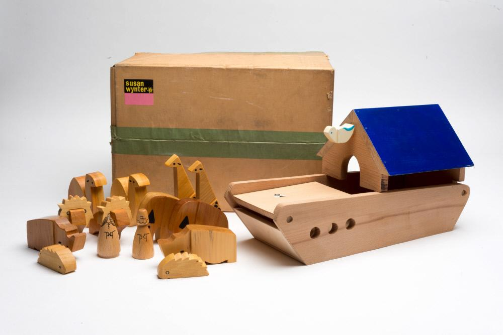 A toy wooden boat and animals, next to a brown cardboard box.