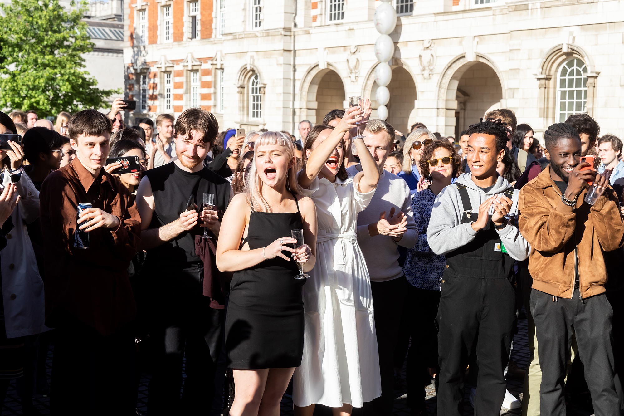 A group of Chelsea students stands in the Parade Ground at Chelsea cheering and shouting in celebration of a prize being awarded. They hold drinks and on the right a student is taking a photo with his mobile phone.
