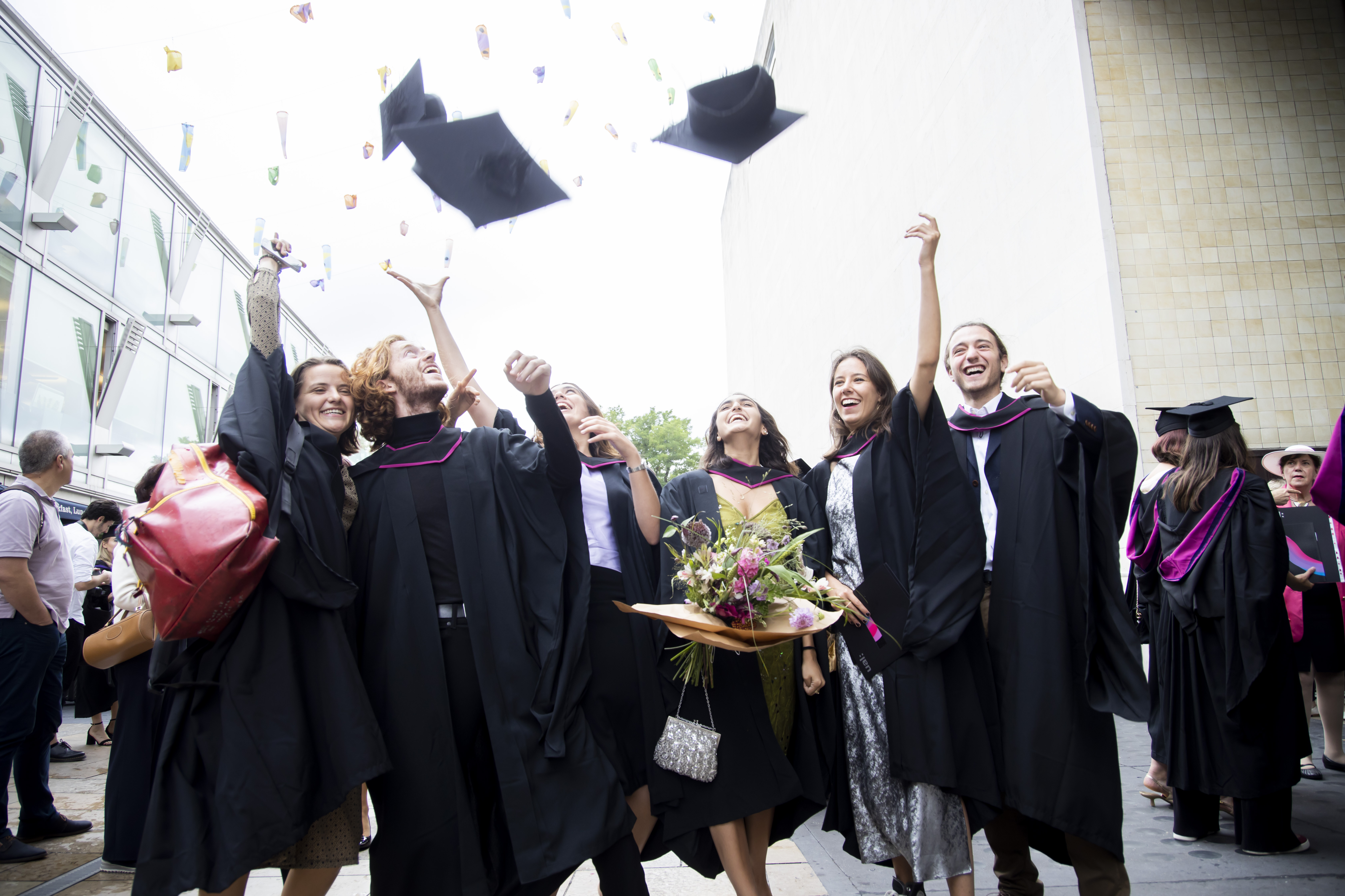 Student throwing mortarboards into the air