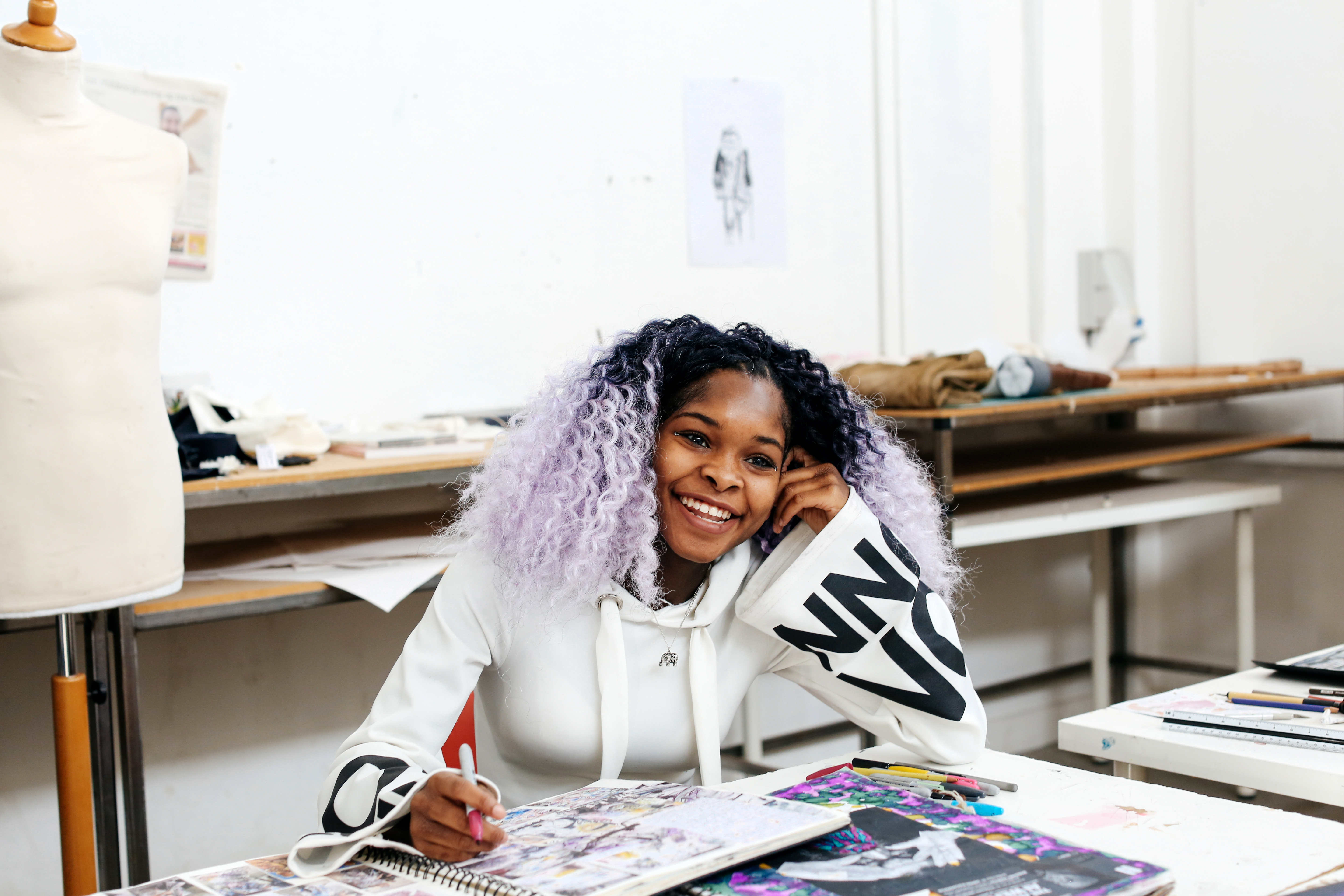 Woman with purple hair, smiling. Her sketchbook is open on the table