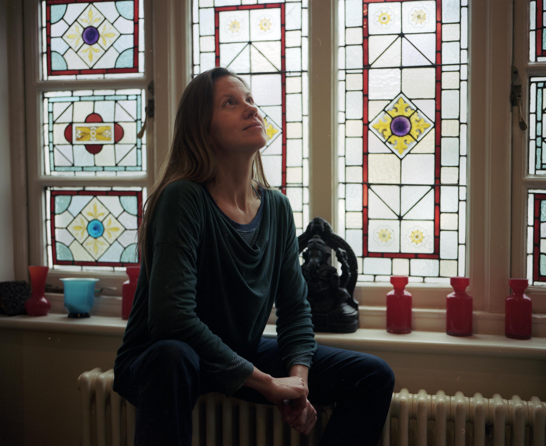 A woman sitting near a stain glass window