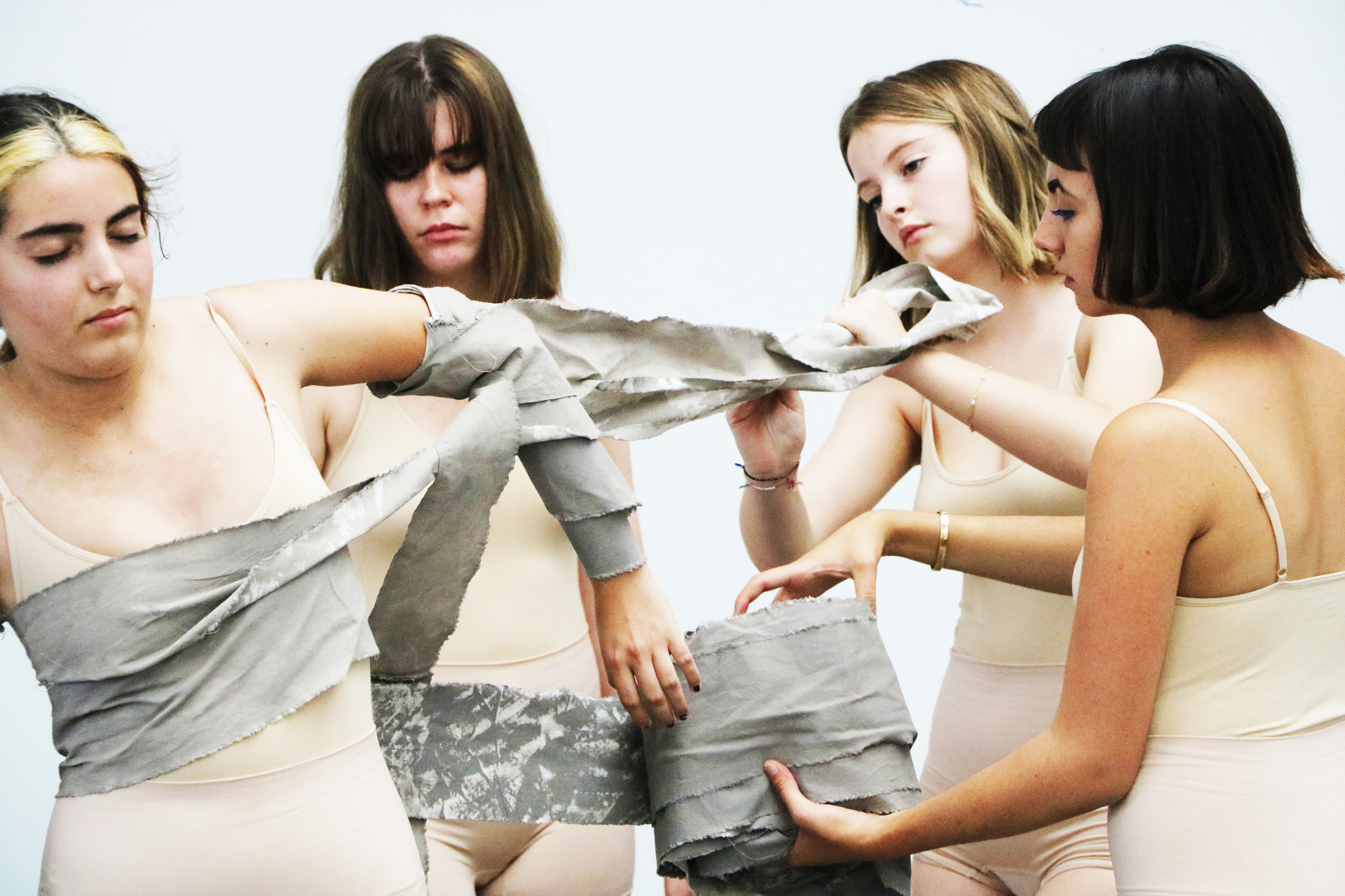 Fashion students performance, three girls wrap a fourth with grey material
