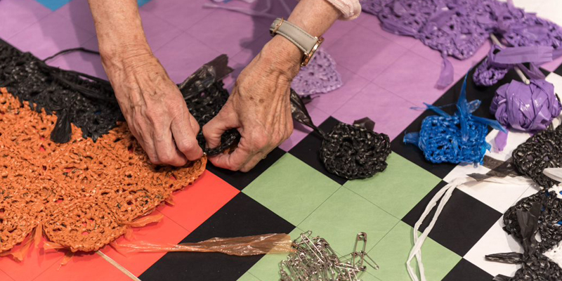 an elderly lady's hands crochetting plastic thread
