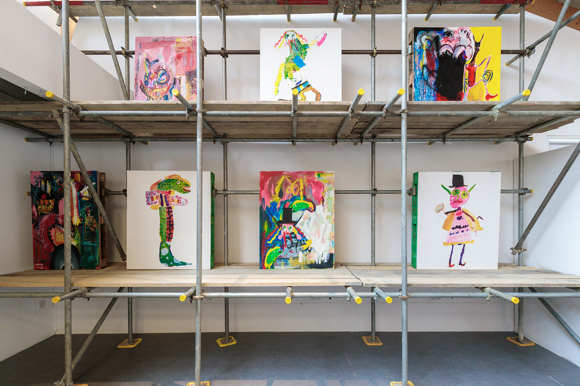 7 paintings displayed on scaffolding