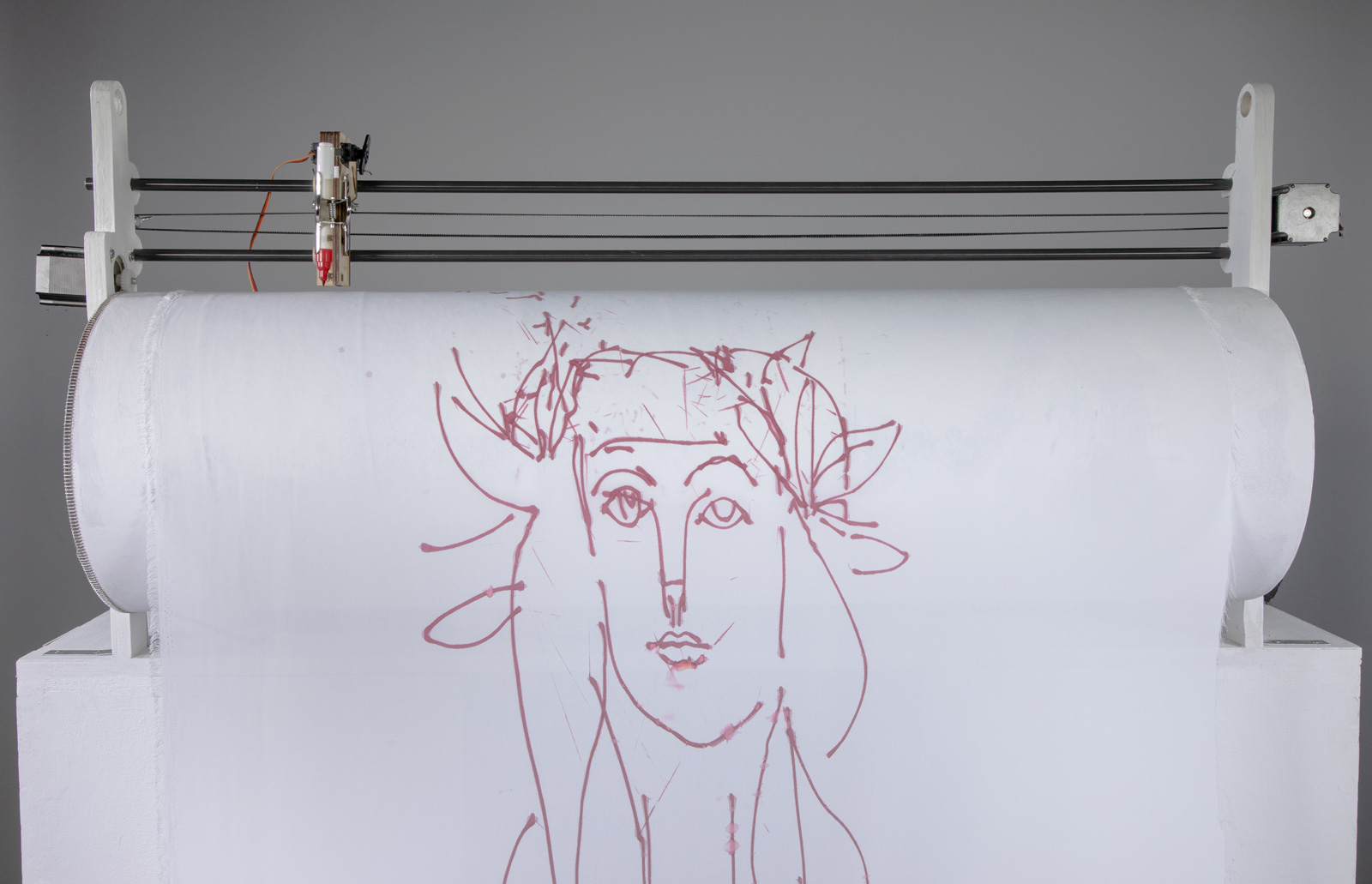 A robot holding sheet of fabric with a drawing of a Picasso-style face, with the sheet of paper on a roller with a pen held