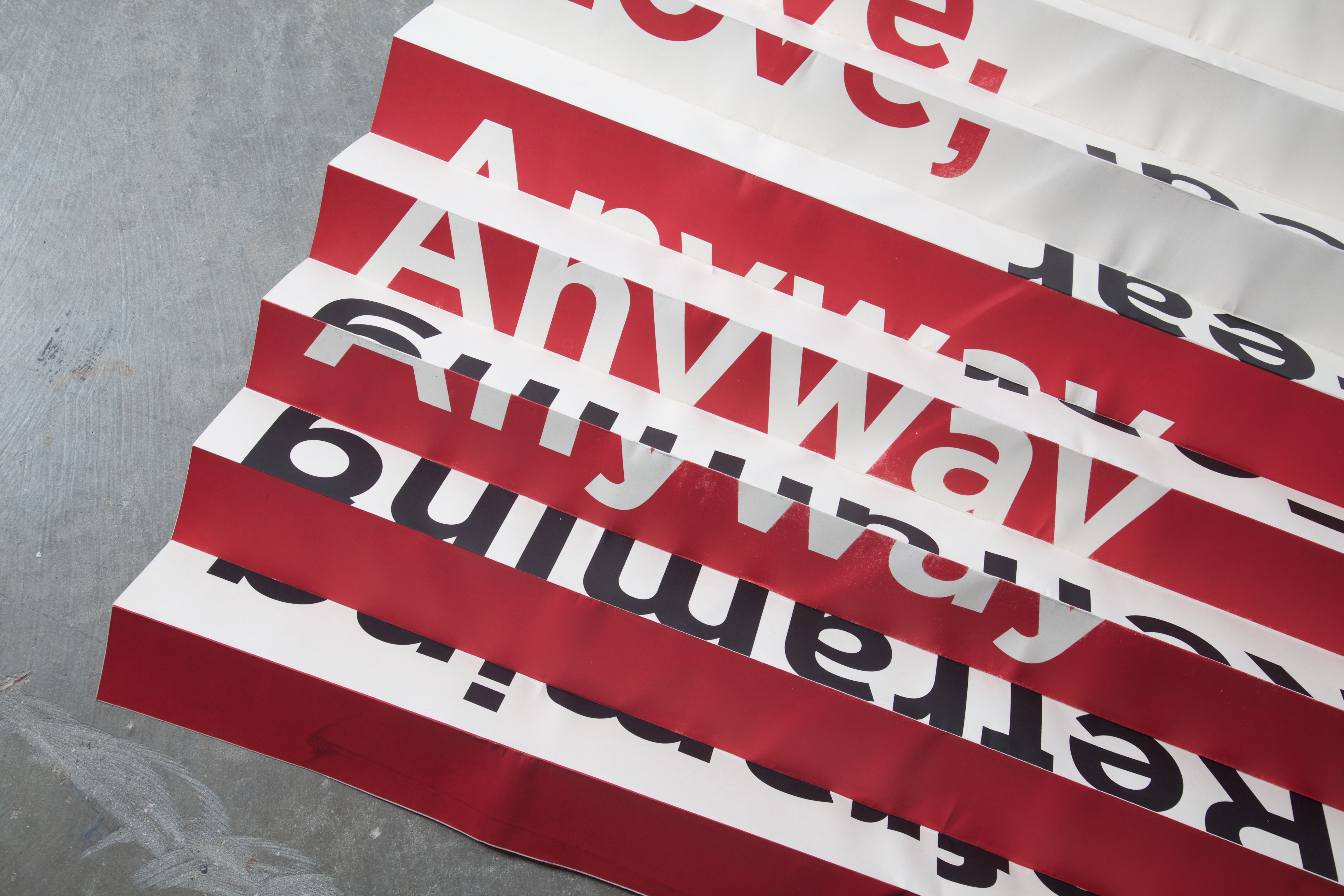 A red and white poster with multiple folds