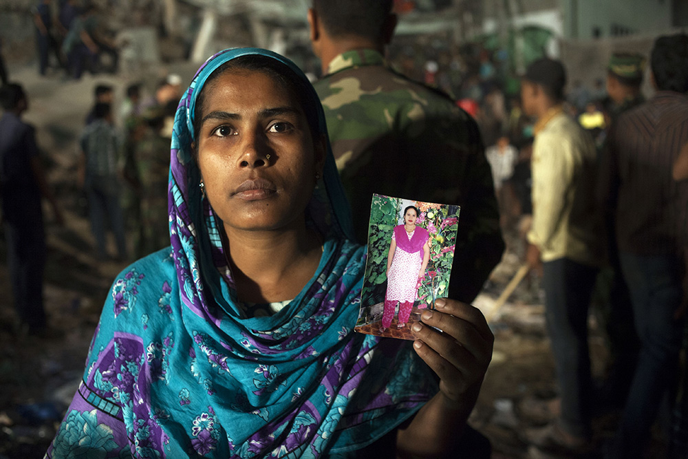 A-woman-holding-a-picture-of-her-missing-relative–at-the-collapse-site—-