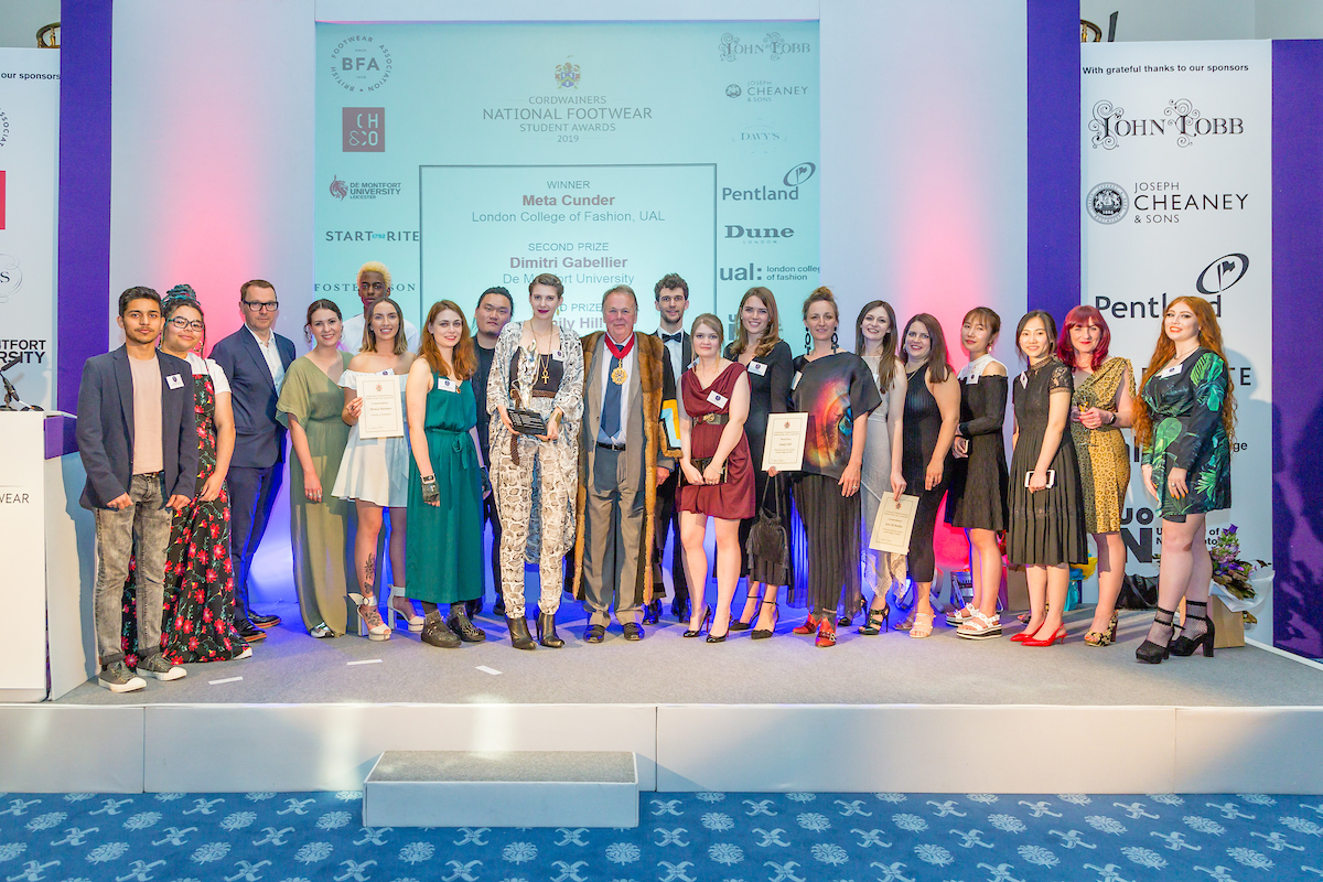 A mixed group of 20 people stand on stage at the Cordwainers National Footwear Student of the Year 2019
